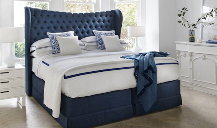 Royal blue divan bed with luxurious buttoned upholstered headboard