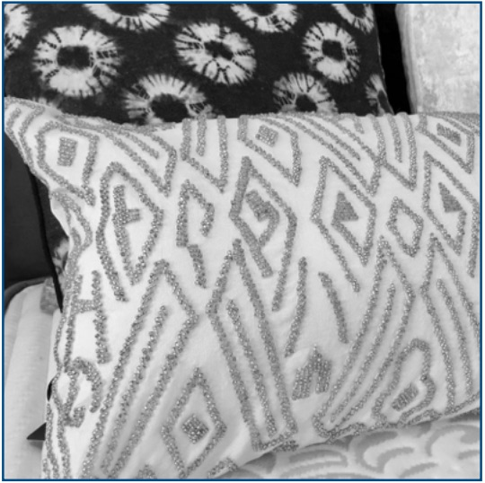 White cushion cover with silver beaded pattern