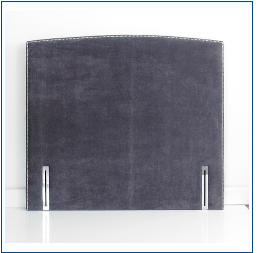 Grey curved upholstered floorstanding headboard with a single row of studs linings its edge