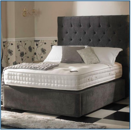Grey upholstered chunky box base bedstead with a buttoned and diamond pleated headboard