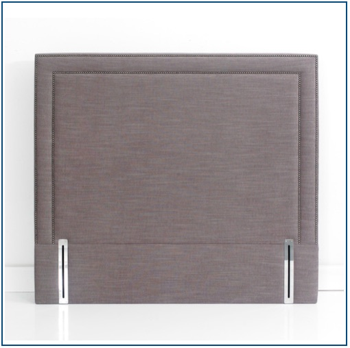Grey rectangular shaped, upholstered floorstanding headboard with two rows of studs outlining the shape