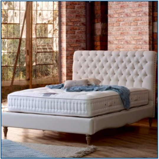 White upholstered bedstead with button and pleated detailing as well as studs lining the edge of the headboard