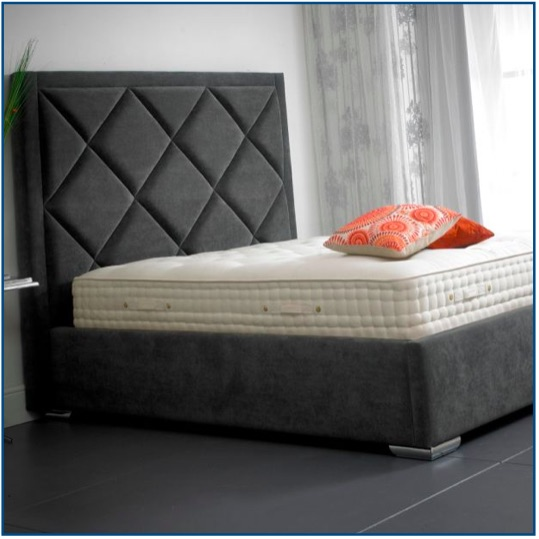 Grey upholstered modern bedstead with a tall, diamond detailed headboard and picture frame surround.