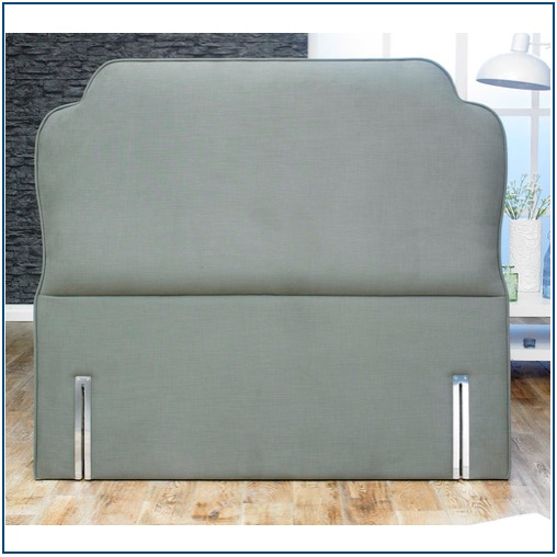 Grey upholstered floor standing headboard with shaped corners and piping around the edge