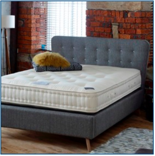 Grey upholstered retro design bedstead with a low headboard and contrast button detailing