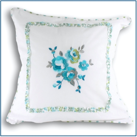 White cushion cover with embroidered green and blue flowers