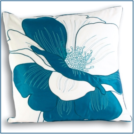 White cushion cover with bright teal flower design