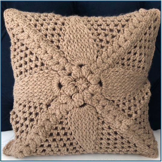 Brown crocheted flower cushion cover